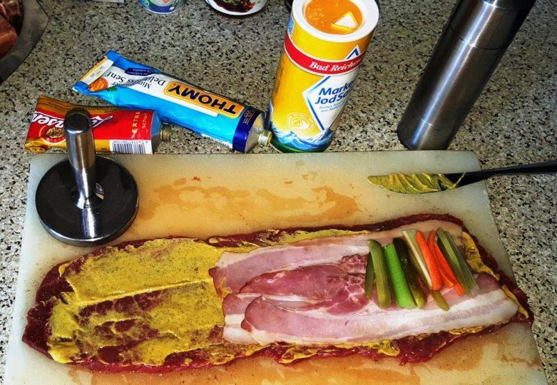 Rouladen leicht plattieren, mit Pfeffer und Salz würzen, dünn mit Senf bestreichen, Geselchtes, Möhren-, Sellerie- und Gurkenstifte auflegen