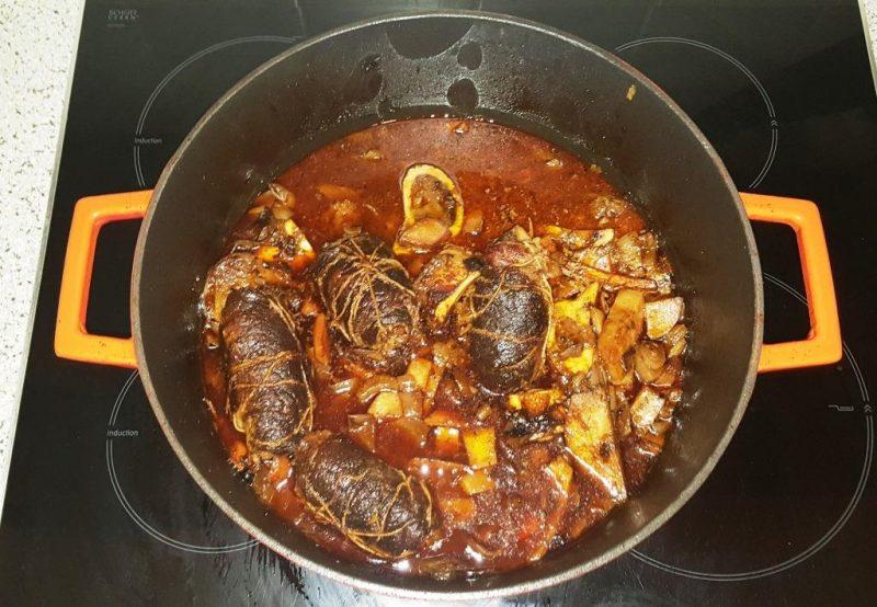 Nach dem Ablöschen Rouladen auf das Knochen-Gemüse-Bett geben, im Ofen schmoren lassen